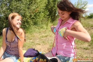 Young lesbians grind their twats together on a blanket down by the lake