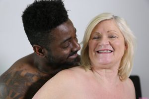 Chubby blonde granny Lacey Starr tastes a black cock before riding it