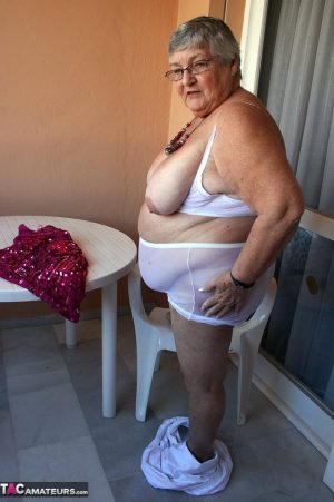 Obese grandmother GrandmaLibby parts her labia lips after disrobing on balcony