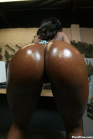 Ebony military doll Baby Cakes oils up her big natural tits and round booty