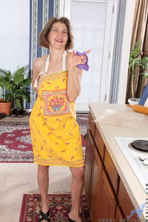 Sassy mature housewife Bobby Bentley toys with a rolling pin wearing an apron