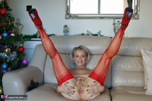 Busty older blonde Sugar Babe toys her pussy in red nylons afore the Xmas tree