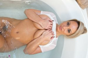 Amateur solo girl Nikki Sims hides her big tits after getting wet in a bathtub