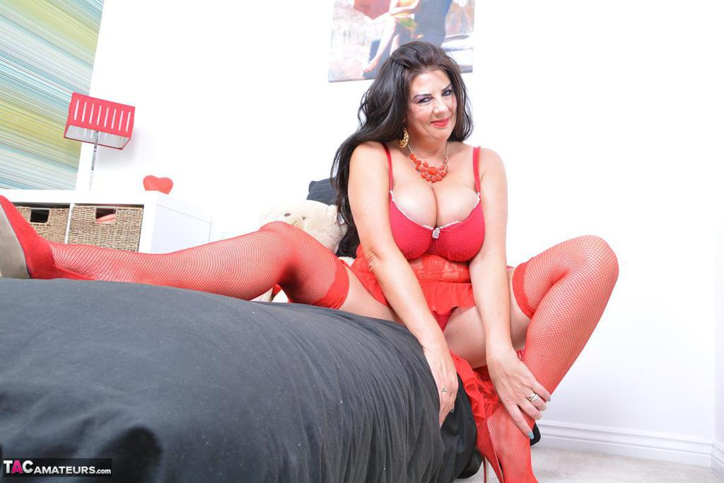 Thick brunette Lu Lu Lush sticks out her tongue while modeling red lingerie