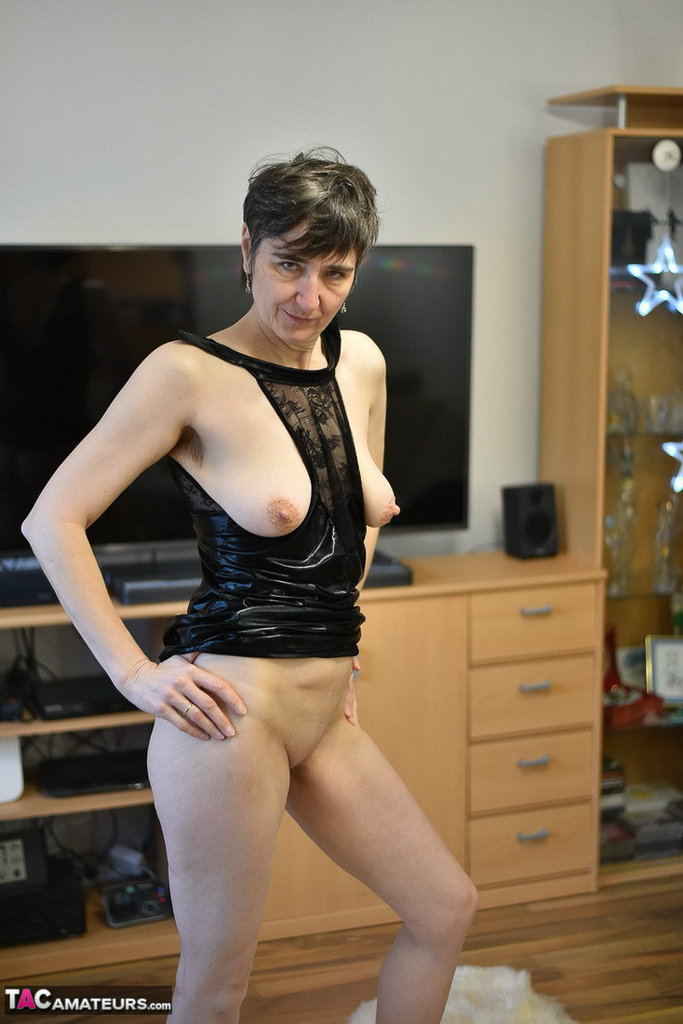 Amateur model with short hair sheds revealing black lingerie to stand naked