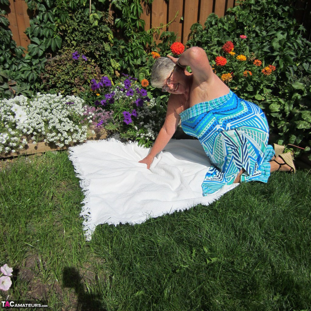 Fat nan Girdle Goddess strips to sheer pantyhose on a blanket by a flower bed
