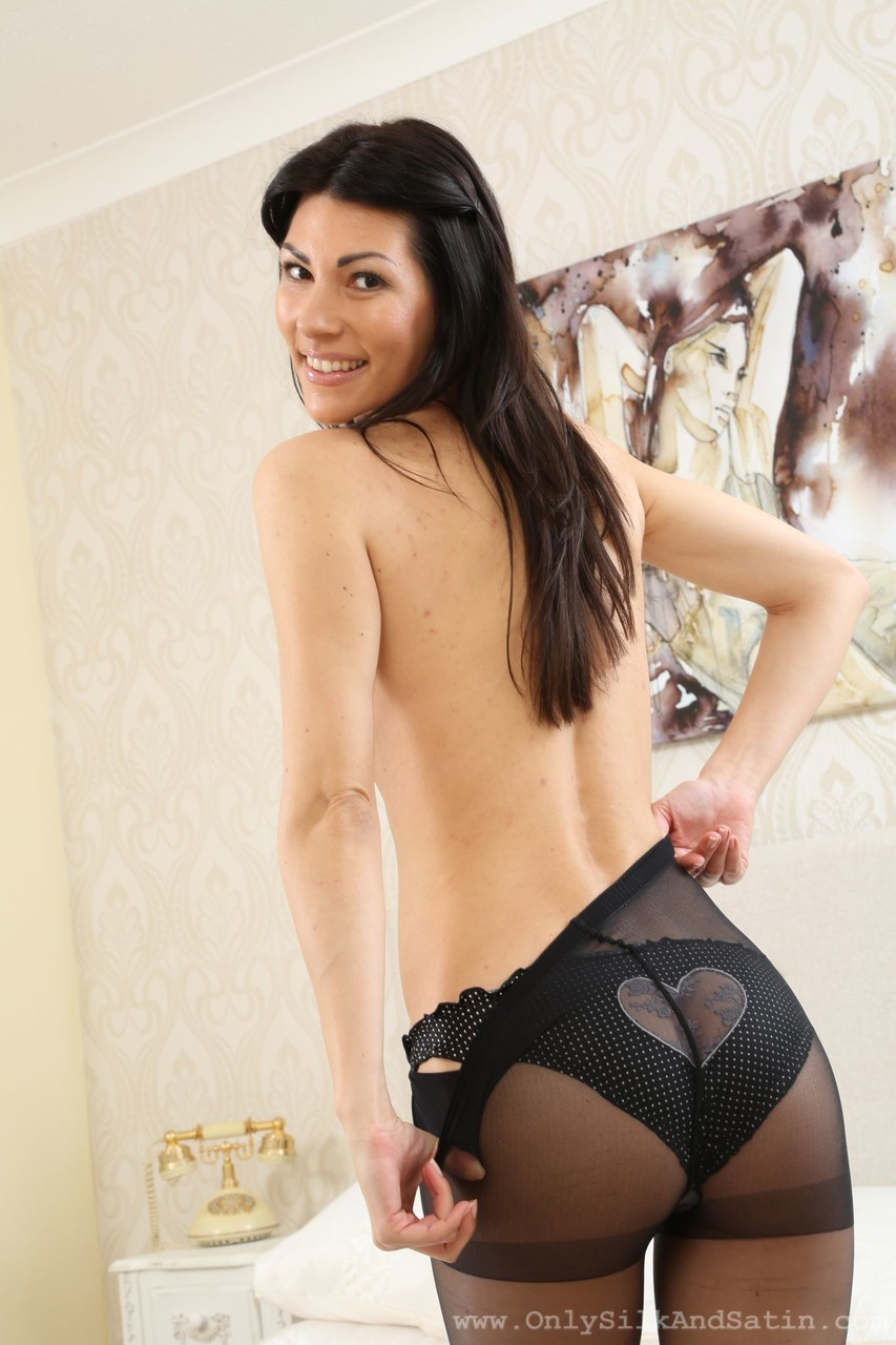 Black haired Sabrina C displays her black pantyhose stockings and breasts