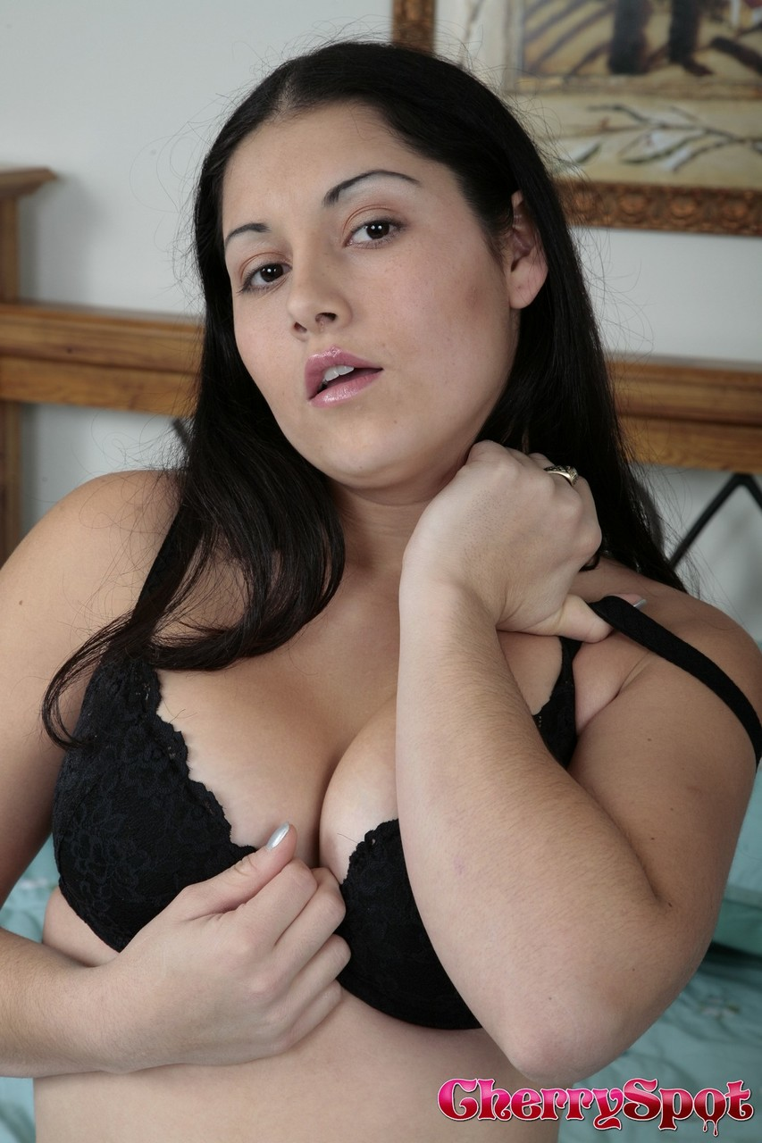 Busty Latina Emma Cummings slides a tiny purple toy between her pussy lips