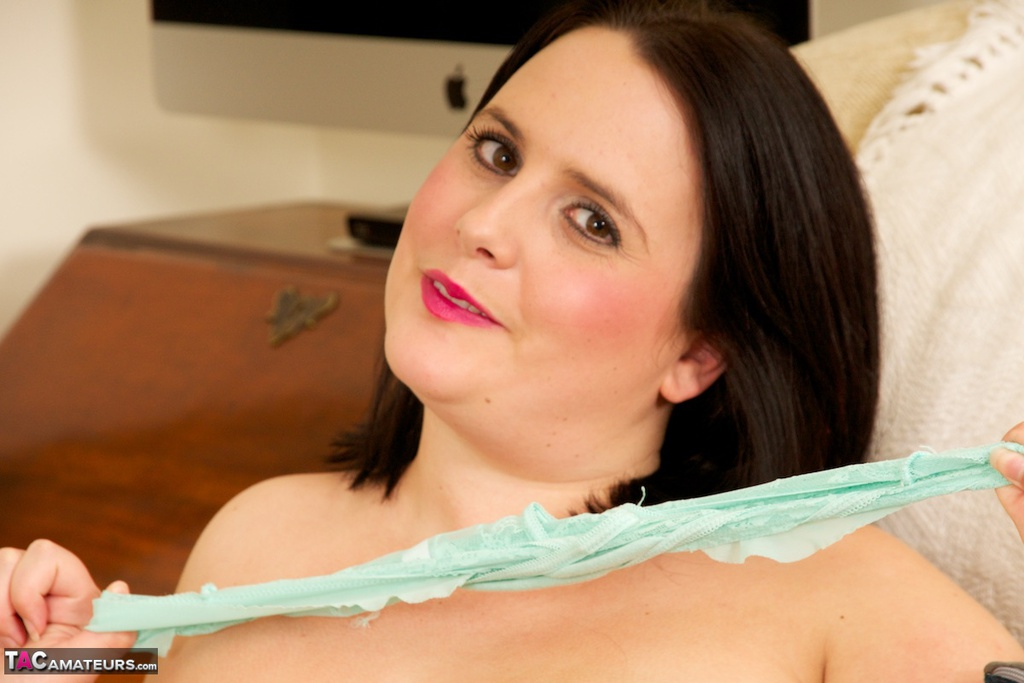 Dark haired BBW toys her shaved pussy after removing sensual lingerie