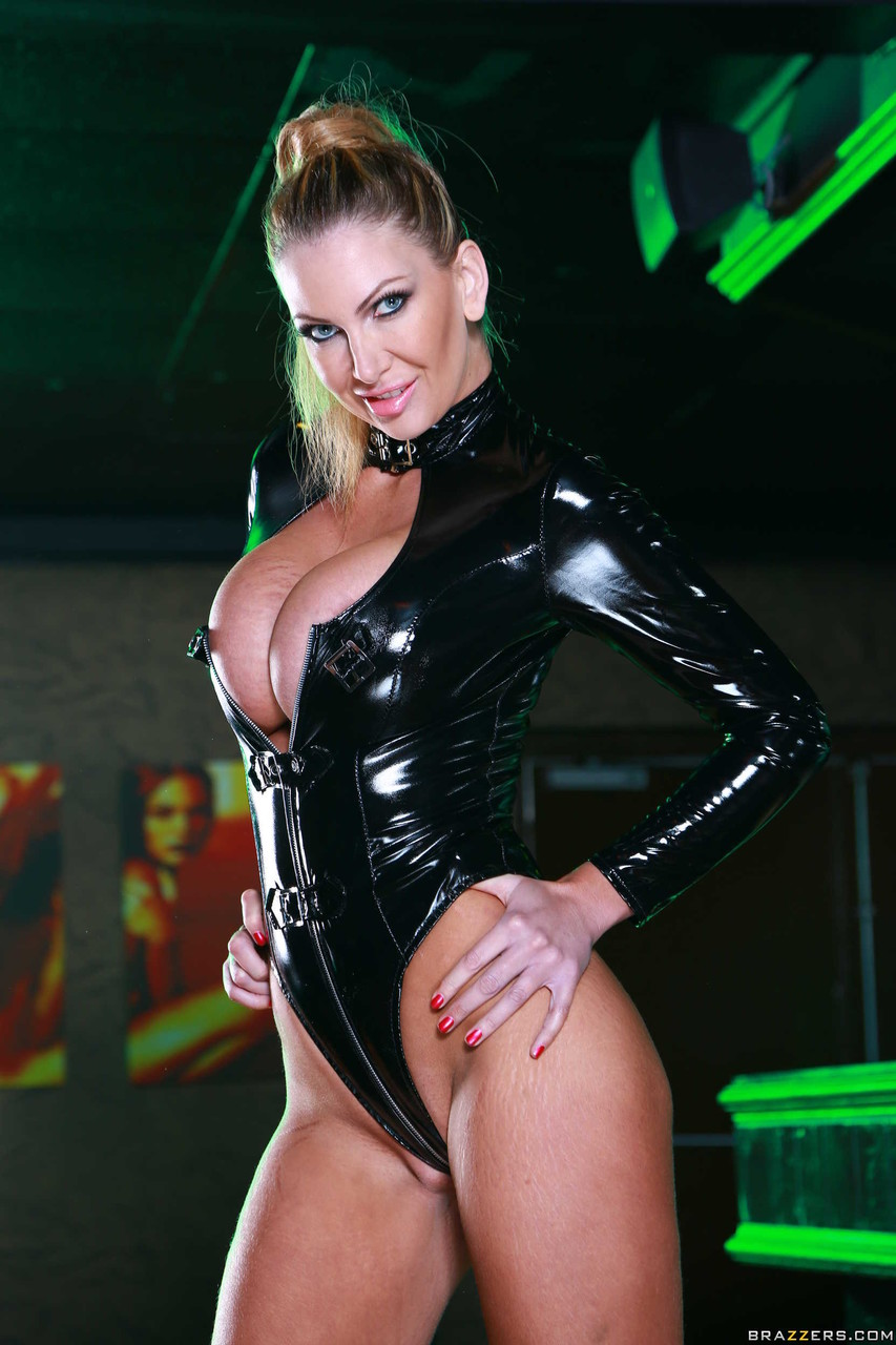 Curvaceous MILF Leigh Darby shows her big melons while posing in latex outfit