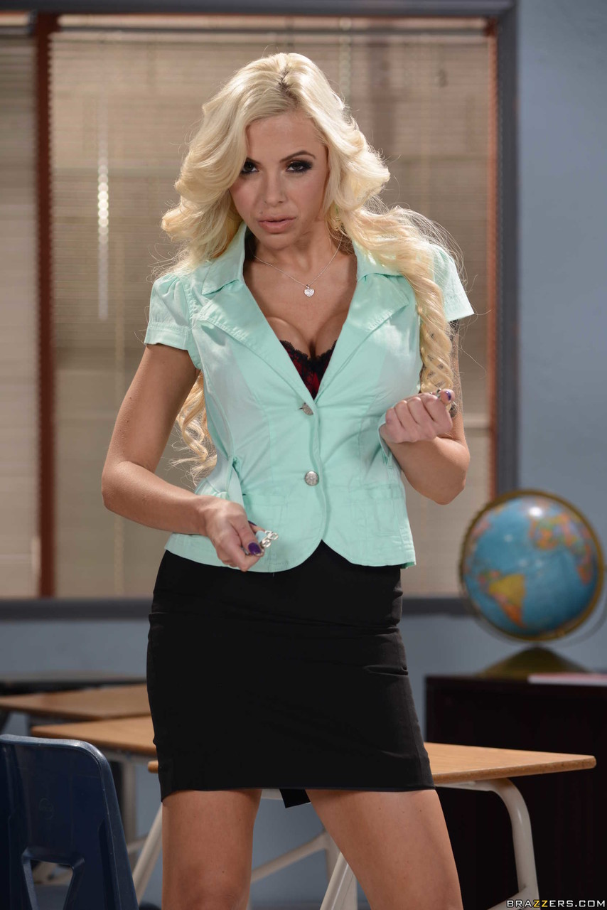 Busty pornstar with arm tattoo Nina Elle reveals her curves in the office