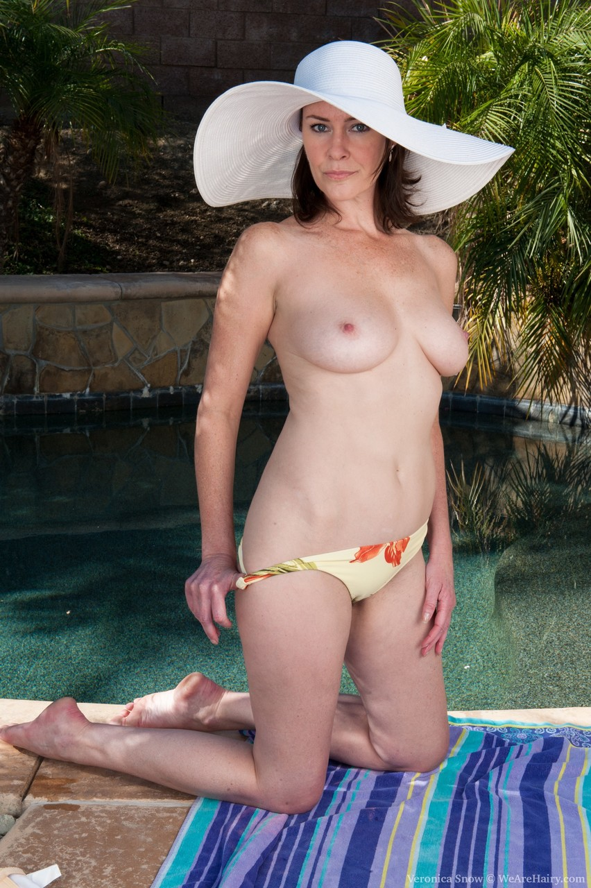 Mature with perfect natural tits Veronica Snow fingers her hairy bush poolside