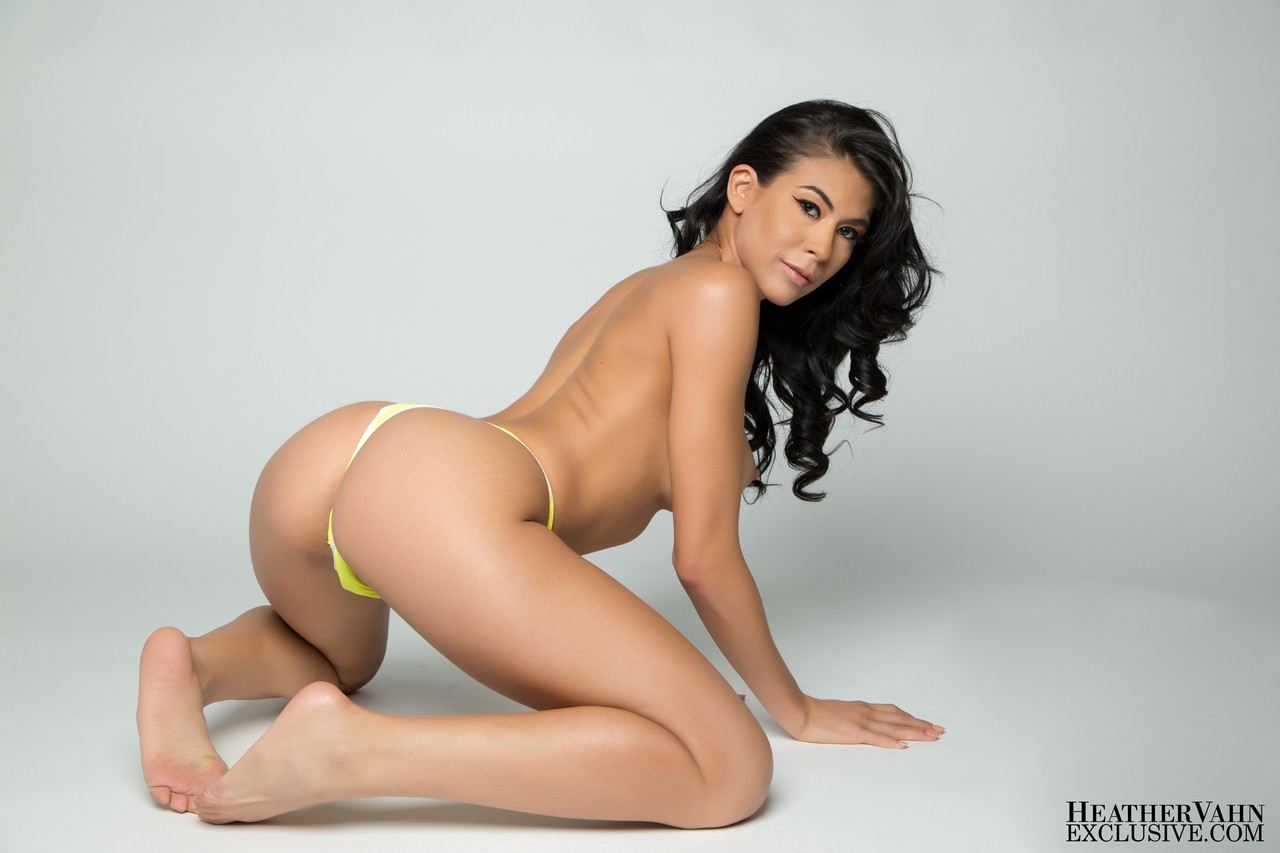 Hot black haired babe Heather Vahn gets herself naked in a white room