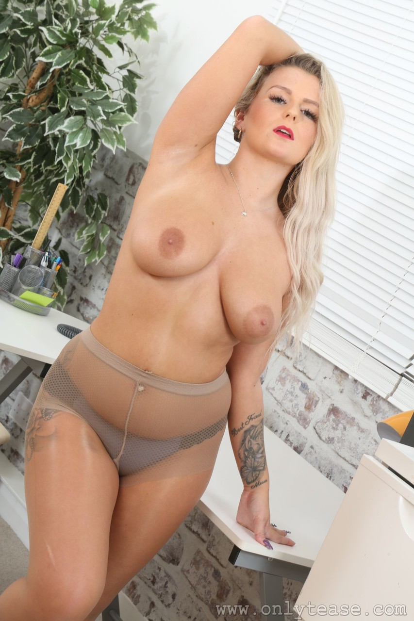Inked blonde secretary Lycia in nylons bares her big tits in the office