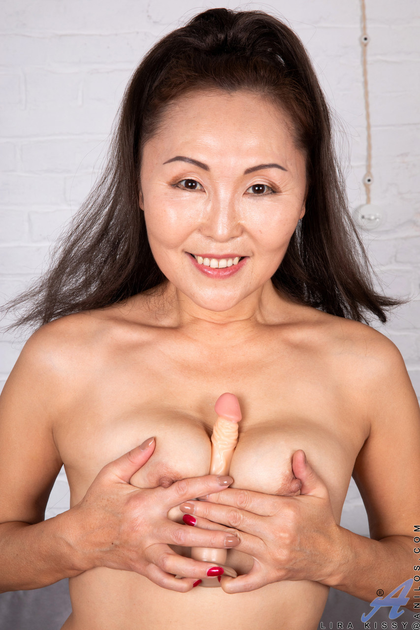 Asian MILF Lira Kissy undresses then toys her shaved pussy with a small dildo