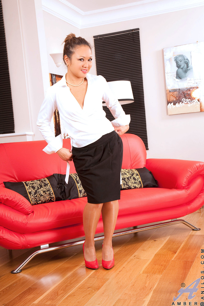 Elegant mature Asian in stockings Amber fingers herself on the red couch