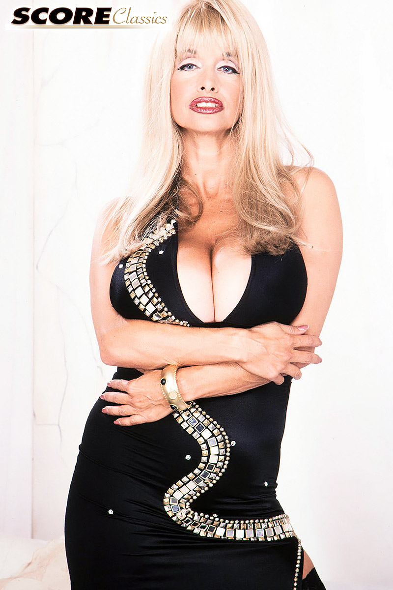 Blond bombshell Alexis Love set hers enhanced breasts free of a long dress